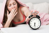 Sleepy young woman in bed with eyes closed extending hand to alarm clock at home — Foto de Stock