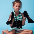 Little girl wearing big mothers shoes — Stock Photo #22264357