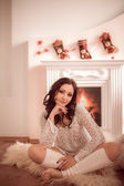 Beautiful young girl sitting beside the fireplace and Christmas tree — Stockfoto