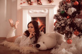 Sexy girl lying beside the fireplace and Christmas tree — Stockfoto