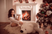 Sexy girl sitting beside the fireplace and Christmas tree — Stockfoto