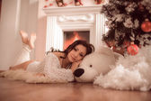 Sexy girl lying beside the fireplace and Christmas tree — Stock Photo