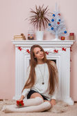 Girl sitting beside the fireplace — Foto Stock
