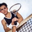 Beautiful young girl rests on a tennis net — Stock Photo #30264145