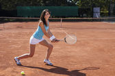 Beautiful girl smiling with a tennis racket — Stock fotografie