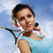 Beautiful girl smiling with a tennis racket — Stock Photo