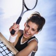 Beautiful young girl rests on a tennis net — Stock Photo #30868857