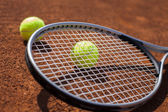 Tennis balls and rocket on court field — Stock Photo