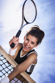 Beautiful young girl rests on a tennis net — Stock Photo