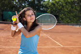 Young girl holding tennis ball on court — Stock Photo