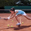 Young girl catching a ball in tennis court — Stock Photo
