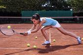 Młoda dziewczyna złapaniu piłki w kort tenisowy — Zdjęcie stockowe