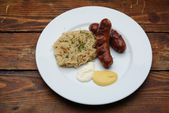 Sausages and old wooden table — Stock Photo