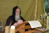 Bearded monk chronicler writes on the historic festival ancient scroll — Stock Photo