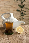 Cup of green tea and white tea kettle — Stock Photo