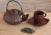 Brown teapot and cup with green tea — Stock Photo
