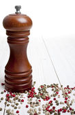 Pepper-mill with peppercorns on white background — Stock Photo