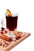 Copo de vinho quente e ingredientes sobre uma mesa de madeira — Foto Stock