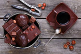 Vase with chocolate, nuts and coffee — Stock Photo
