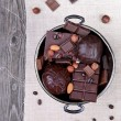 Chocolate in a metal vase on a background of gray canvas and woo — Stok fotoğraf