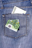One hundred euro note in the back pocket of jeans full of holes. — Stock Photo
