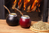 Hot mate in calabashes on the background the fireplace — Stock Photo