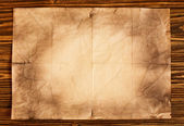 Old paper on brown wooden background — Stock Photo