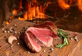 Beef steak on a wooden table on a background of fire — Stock Photo