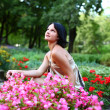 Stock Photo: Beautiful girl in park with colorful flowers