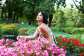 Beautiful girl in park with colorful flowers — Stock Photo