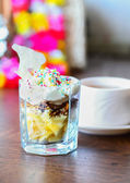 Fruit dessert with colorful sprinkles & cup of tea — Stock Photo