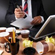 BusinessmStapling Papers at Messy Desk — Stock Photo #12124681