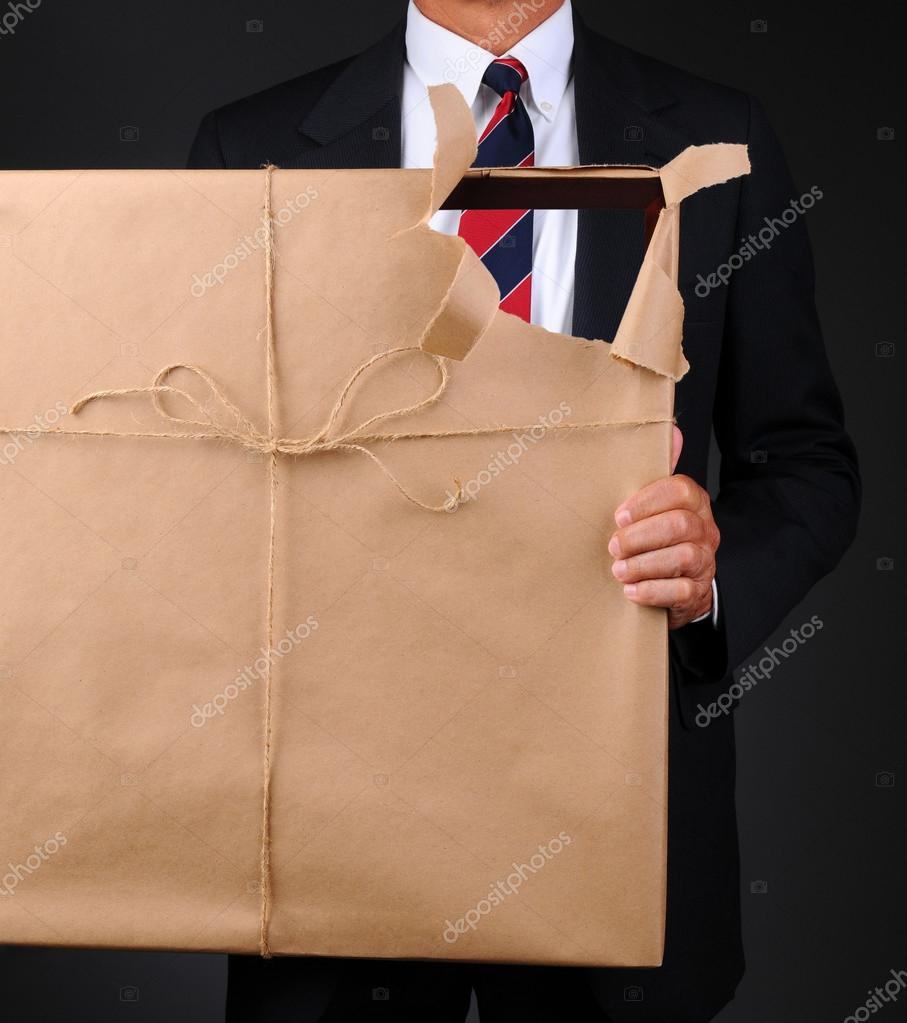 Closeup of a man holding a picture frame wrapped with brown paper in front of his body. Paper is torn revealing as see through hole with the man visible thru the ope — Stock Photo #12124569