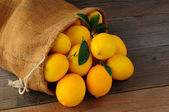 Lemons In Burlap Sack on Wood — Stock Photo