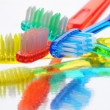Toothbrushes on Reflective Surface - 图库照片