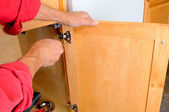 Attaching Hinge to Cabinet — 图库照片