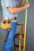Contractor Standing on Ladder Measuring — Stock Photo