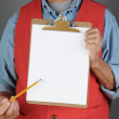 Store Worker Pointing to Clip Board — Stock Photo