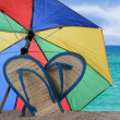Sandals and Umbrella Stuck in the Sand — Stockfoto