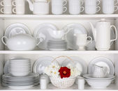 White Plates in Cupboard With a Basket of Roses — Stock Photo