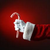Jultomten som innehar stora sockertopp över ett ljus till mörk röd ba — Stockfoto