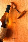 Chardonnay Bottle and Corkscrew on Wood Background — Stock Photo