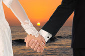Bride and Groom Holding Hands at Sunset — Stock Photo