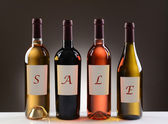 Wine Bottles With Labels Spelling Out Sale — Stock Photo