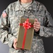 Soldier Holding Christmas Present — Stock Photo #37020001