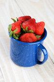 Blauwe beker vol met vers geplukte rijpe aardbeien — Stockfoto