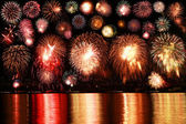 Colorful fireworks reflect from water — Stock Photo