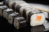 Sushi rolls on black dish — Stock fotografie
