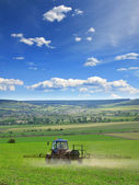 Farming tractor plowing and spraying on field vertical — Stock Photo