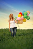 Young woman with colorful balloons on a green meadow — Stock Photo